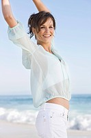Woman jumping on the beach and smiling