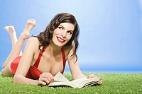 Young woman lying on artificial grass with book
