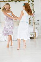 Two flower girls playing in a bedroom