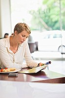 Businesswoman sitting in a restaurant and reading a magazine