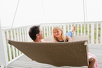 Girl sitting on a swing with her father