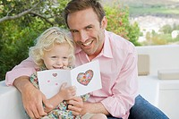 Portrait of a man with his daughter holding a greeting card