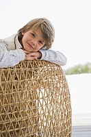 Portrait of a boy leaning on a wicker chair