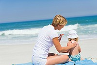 Woman applying suntan lotion on her daughter on the beach