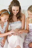 Bride showing her wedding ring to girls