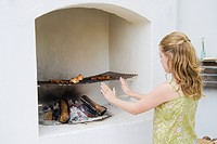 Girl cooking kebab in fireplace