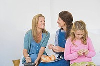 Two women preparing food with a girl at home