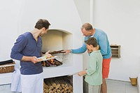 Two men with a boy cooking kebab at fireplace