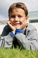 Boy lying on grass and smiling
