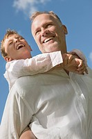 Boy riding piggyback on his father