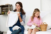 Woman and her daughter holding pillow covers
