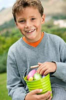 Boy holding a container full of Easter eggs