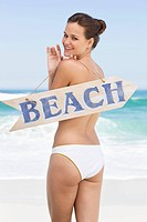 Rear view of a woman holding a BEACH signboard