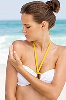 Woman applying suntan lotion on her shoulder (thumbnail)