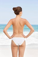 Rear view of a woman standing on the beach and looking at a view