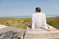 Rear view of a man sitting on a boardwalk on the beach