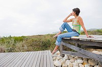 Woman sitting on a boardwalk and thinking
