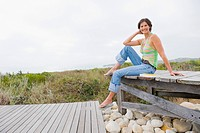 Woman sitting on a boardwalk