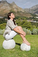 Woman sitting on round stones and smiling