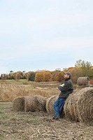 Farmer sitting on hay bale