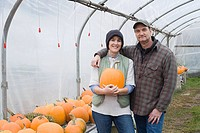 Farmer couple in greenhouse with pumpkins