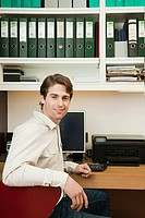 Young man sitting in home office