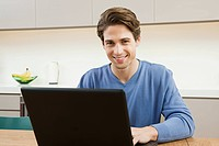 Young man sitting at table with laptop