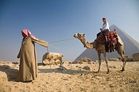 Young woman tourist on a camel being led by a guide at the Pyramids of Giza, Cairo, Egypt