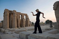 Woman tourist walks like an Egyptian at the Ramesseum, Luxor, Nile Valley, Egypt