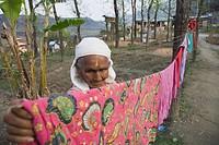 Elderly woman hanging clothes, Pokhara, Chitwan, Nepal