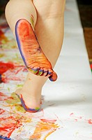 Stock photo of a 3 year old girl enjoying some creative play with feet paints