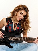 Young woman playing guitar electronica