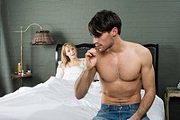 Man brushing teeth in bedroom