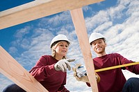 Woman and man measuring construction frame