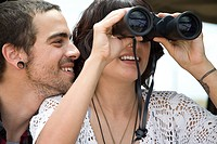 Young couple with binoculars (thumbnail)