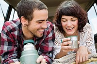Couple having drink from flask