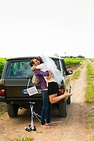 Newlywed couple kissing by vehicle