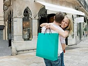 Woman holding shopping bag hugging man