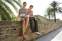 Man and woman sitting and reading on wall (thumbnail)