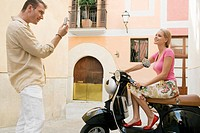 Man photographing woman on scooter