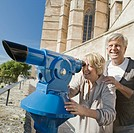 Man and woman using coin_operated binoculars