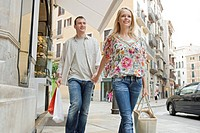 Man and woman holding hands walking with shopping bags