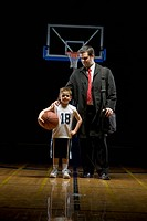 Young boy standing on basketball court with his father