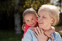 Portrait of grandmother and granddaughter outdoors
