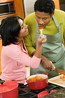 African American man tasking wife´s sauce in kitchen
