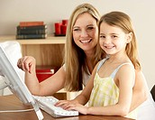 Mother And Daughter At Home Using Computer