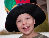 This cute 4 year old Caucasian boy with freckles and an earring is happy and smiling while wearing a colorful wacky hat Background is intentionally bl...