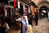 An elderly man walks through a market in the old city section of Jerusalem