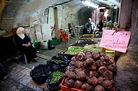 A woman selling olives and more at a market in the old city section of Jerusalem