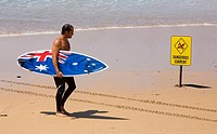 An Australian surfer reads danger surf sign